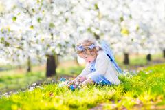 Curly toddler girl in fairy costume playing in fruit garden Stock Photos