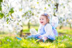 Curly toddler girl in fairy costume playing in fruit garden - stock photo