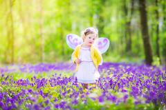 Toddler girl in fairy costume in bluebell forest - stock photo