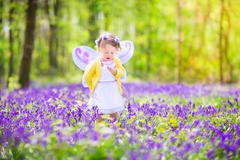 Toddler girl in fairy costume in bluebell forest Stock Photos