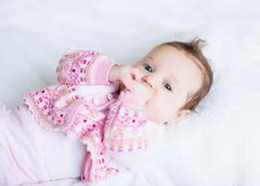 Sweet little baby girl playing with her hands Stock Photos