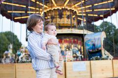 Cute boy and his baby sister enjoying amusement park - stock photo
