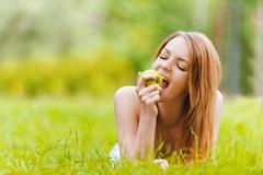 Young woman lying on grass and bit apple Stock Photos