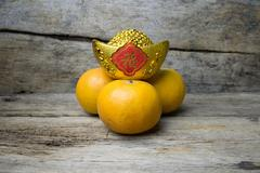 Mandarin oranges with decorative gold nugget (Foreign text means Good Luck) - stock photo