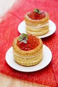 Tartlets with red caviar on plate. - stock illustration