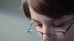 Boy with myopia reading, gazing and concentrating while wearing eyeglasses Stock Footage