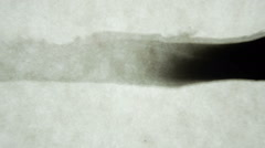 Thin Strip Of Ink Bleeding Into Parchment Paper Stock Footage