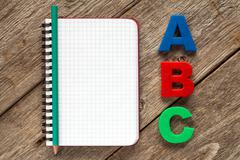 Notebook with pencil and ABC letters - stock photo