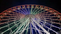 Spinning ferris wheel at night with lights, low angel Stock Footage
