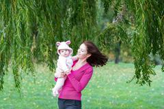 Mother and daughter standing under a colorful willow tree on a windy day Stock Photos