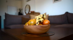 Dolly in, fruit bowl, bananas, oranges, living room coffee table, medium shot Stock Footage