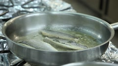 Cook checking pieces of fish that are in the pan Stock Footage