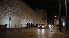 Cars enter old Jerusalem walls, people walk around, nighttime, Israel Stock Footage