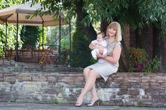 Elegant lady in a formal dress holding a baby in the garden - stock photo