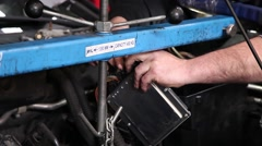 Car mechanic checking the cables from the control unit of car Stock Footage