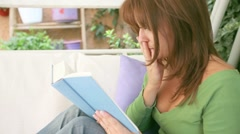 A beautiful girl reading a book exciting, adventurous and suspense Stock Footage