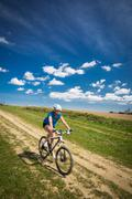 Pretty, young female biker outdoors on her mountain bike (motion blurred imag Stock Photos