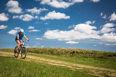 Pretty, young female biker outdoors on her mountain bike (motion blurred imag - stock photo