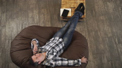 The man lies on a sofa and talking on the phone, feet on the table Stock Footage