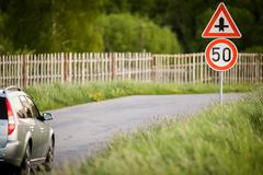 Car on a country road with limited speed and crossroad sign Stock Photos