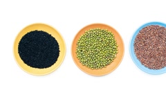 Three colored bowls with seeds panning - stock footage