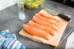 Stock Photo of Young woman seasoning a salmon filet in her modern kitchen, preaparing a heal