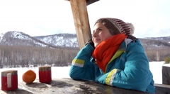 Young girl at a picnic in the winter, sitting in the gazebo, mountains in the - stock footage