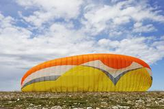 Paraglider canopy on the ground before a take-off - stock photo