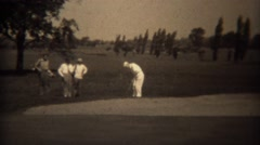 1938: Golfer pitch shot over sand trap to green with friends watching.  TRYON, - stock footage