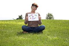 Aging hippie holding a sign with a message for the younger generation:  Save  - stock photo