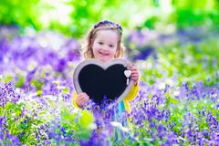 Child playing in bluebells forest. Little girl holding heart shape chalk board - stock photo