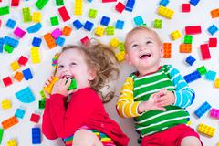 Kids playing with colorful blocks Stock Photos