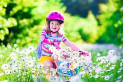 Little girl riding a bike Stock Photos