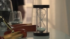 Man's come to the table and turned the sand clock to ON. - stock footage