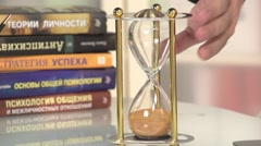 The hand turns sand clock to start. - stock footage
