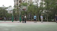Senior men play basketball on a court in Taipei, Taiwan - stock footage