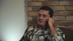 A man resting in a chair and talking on a smartphone Stock Footage