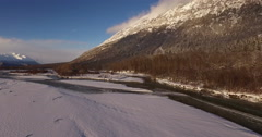 Snowy Scenic Riverbank Lateral Aerial with Tracks 4K Stock Footage