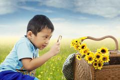 Child observe flowers with magnifying glass - stock photo
