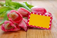 Pink tulips with  card on wood background. - stock photo