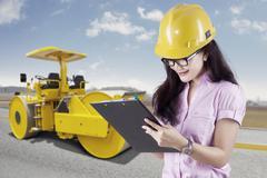 Female engineer and road roller Kuvituskuvat