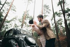 Romantic fairytale wedding couple kissing and embracing in pine forest near - stock photo
