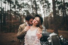 Stock Photo of Romantic fairytale wedding couple kissing and embracing in pine forest near