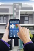 Male hand using smart home app at home Stock Photos