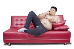 Obese man eats two hamburger on sofa - stock photo