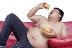 Obese man enjoy two hamburger on the couch - stock photo