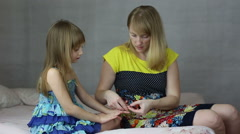Mom puts star stickers on daughters nails - stock footage