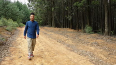 Smiling Funky African or African American man walking on road in nature Stock Footage