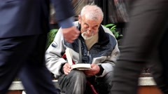 Lonely old man reading a book on a pedestrian street Stock Footage