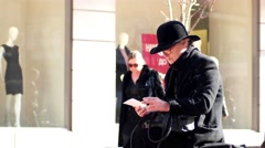 Lonely old woman in a black coat and a hat with a cigarette reads a letter - stock footage
